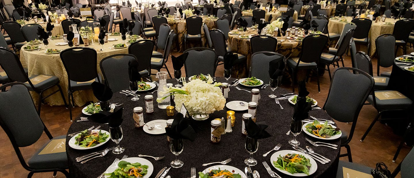 empty banquet room with salads at place settings