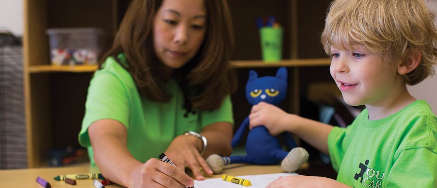 Woman and young child in bright green shirts, coloring with crayons.