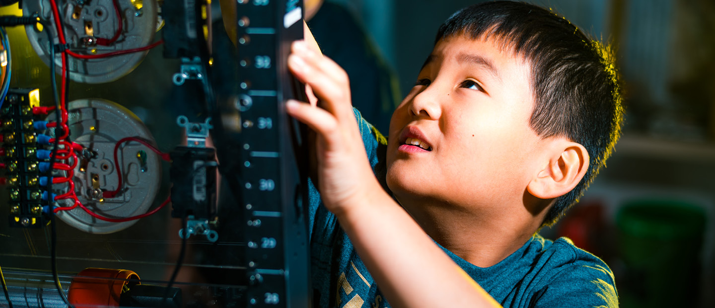 Young boy working on a piece of electrical equipment.