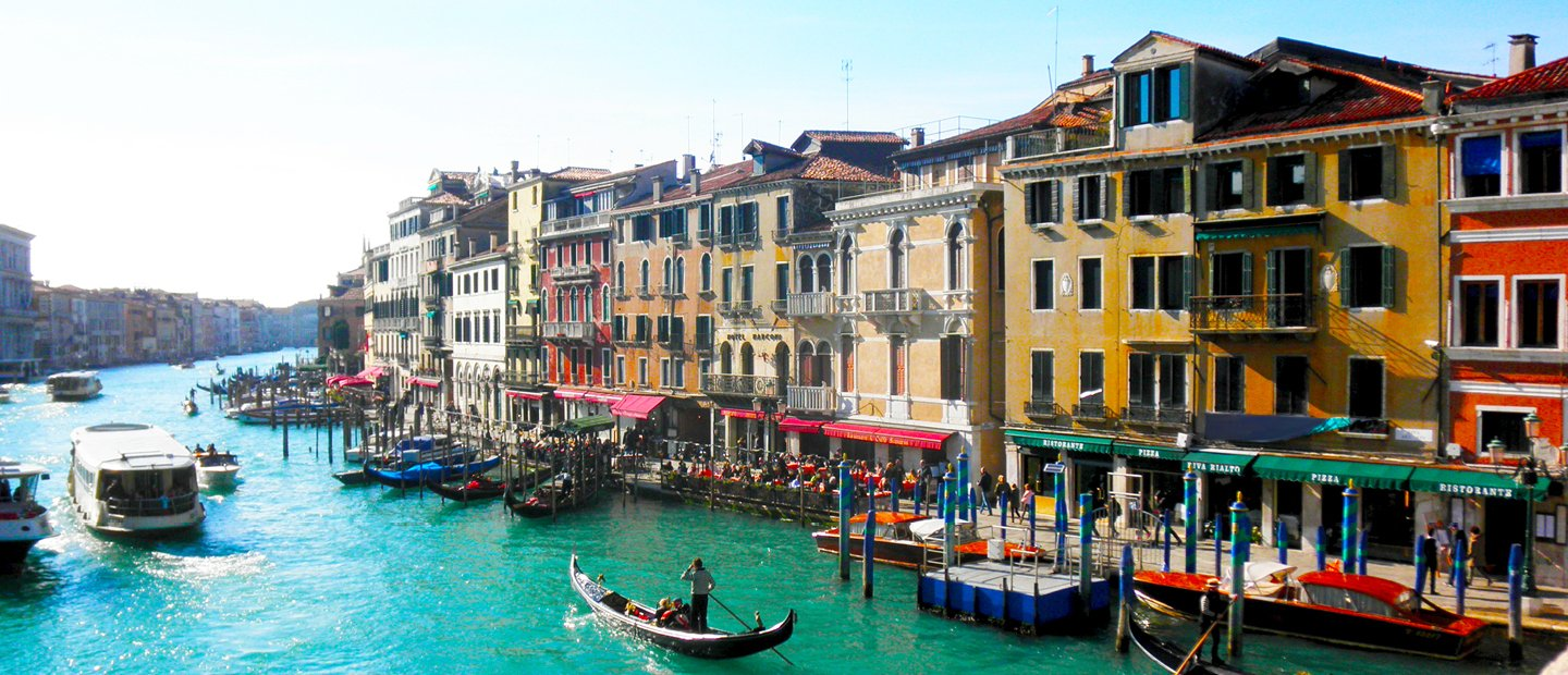 colorful buildings along either side of a river with boats in it, in Italy
