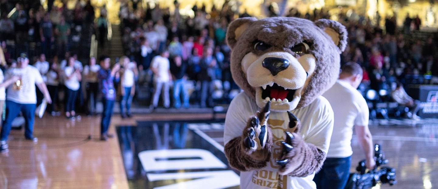 Grizz bear mascot standing on an athletic court with people seated in the stands