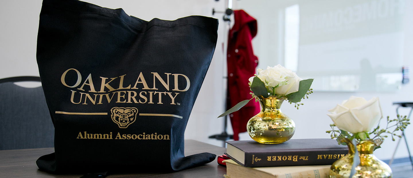 Oakland University Alumni Association bag on a table next to books and flowers in vases.