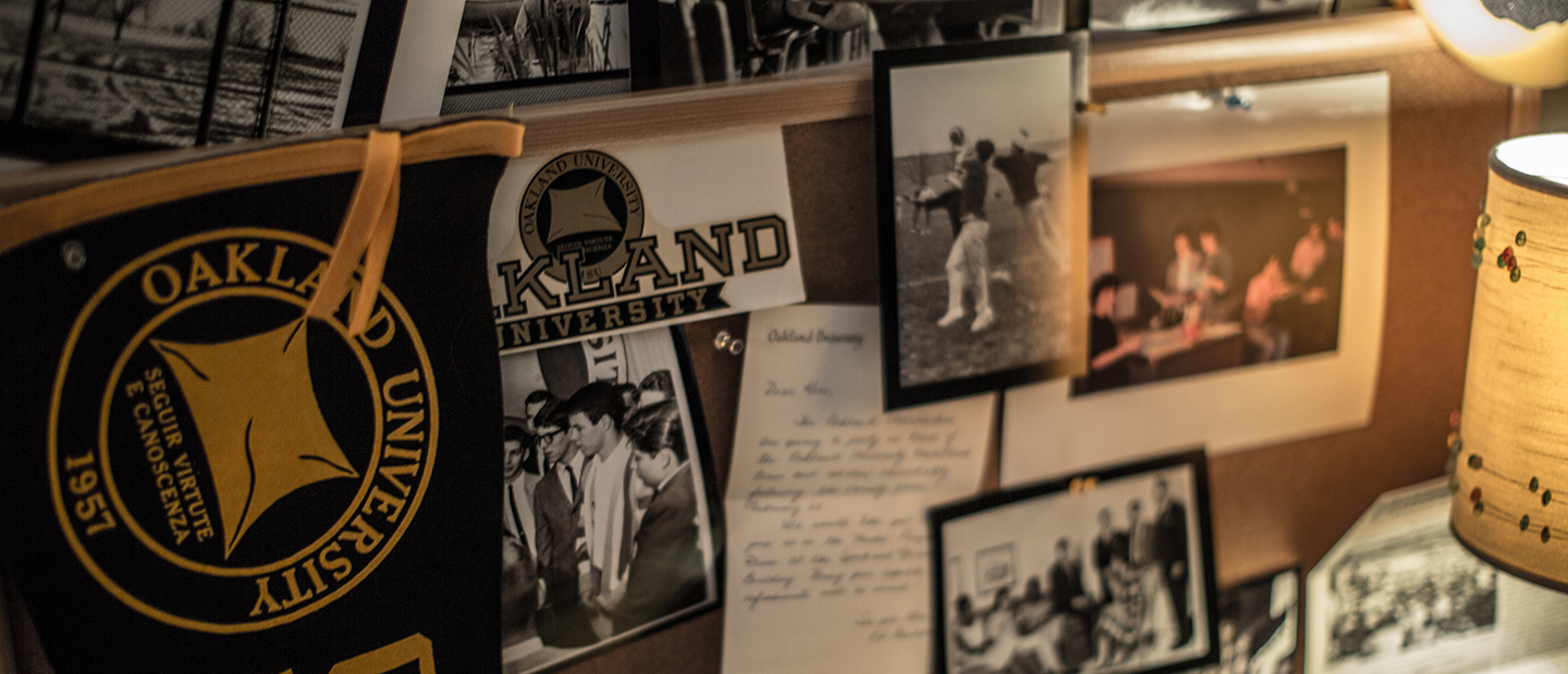 multiple black and white photos and Oakland University memorabilia hanging on a cork board