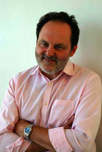 man in a pink shirt with his arms crossed, smiling at the camera