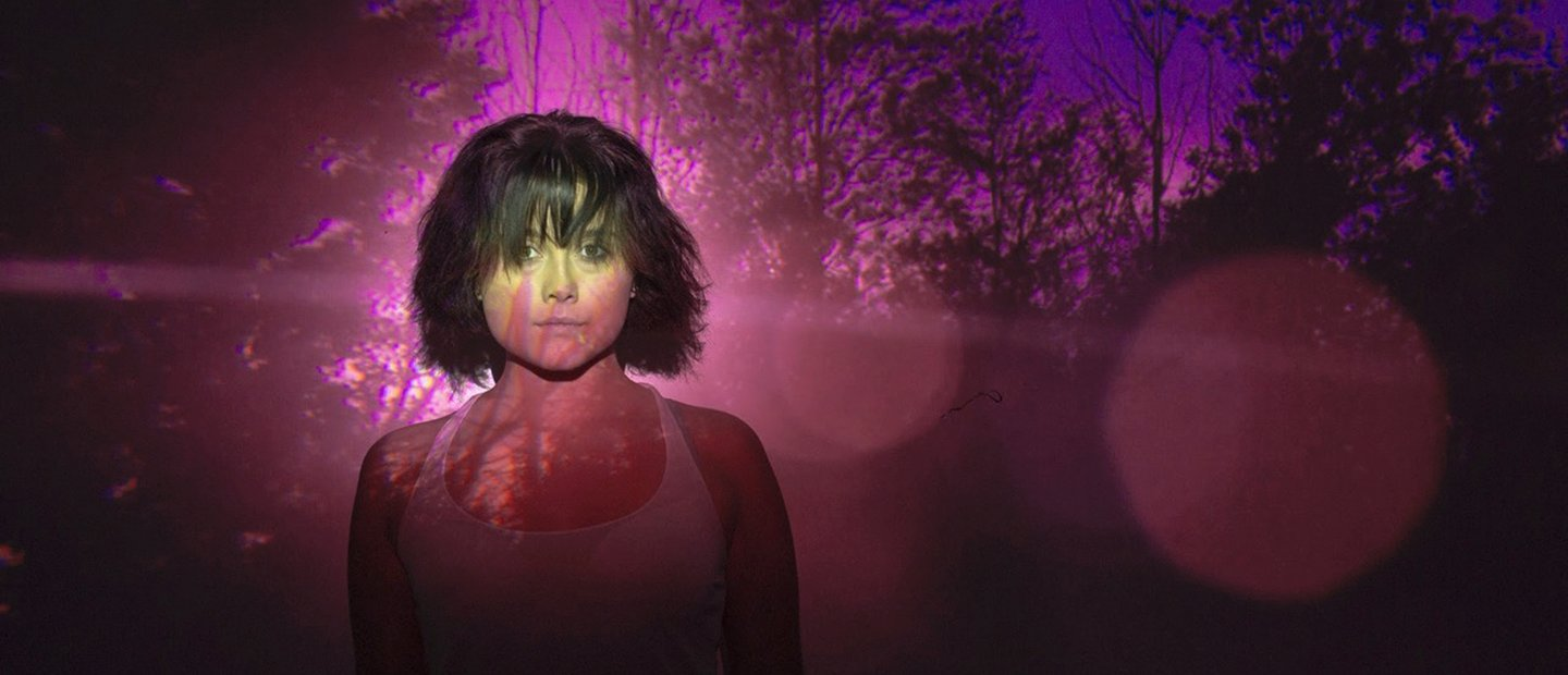 woman standing in front of an image of trees with purple and red lighting