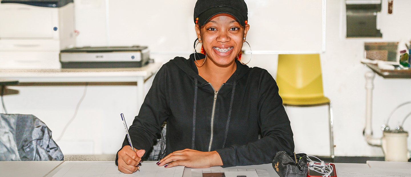 woman seated at a desk with pen and paper, smiling at the camera