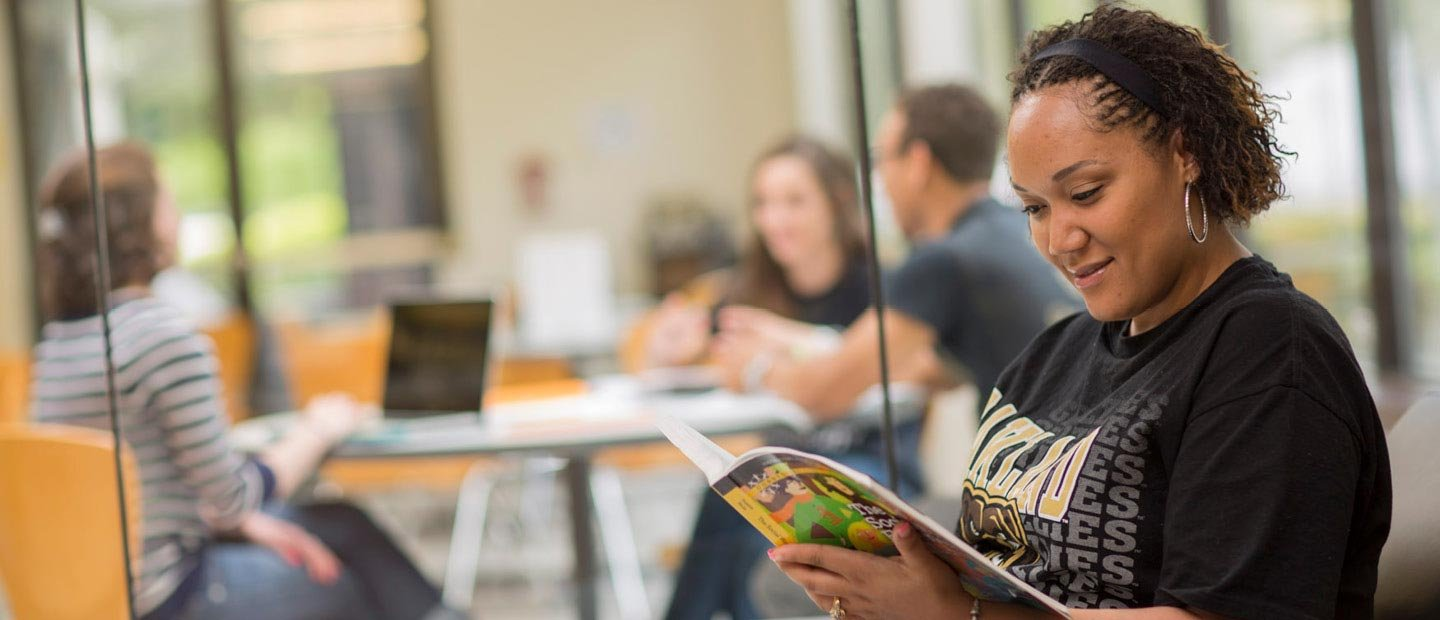 female student wearing a black Oakland University shirt, reading a book