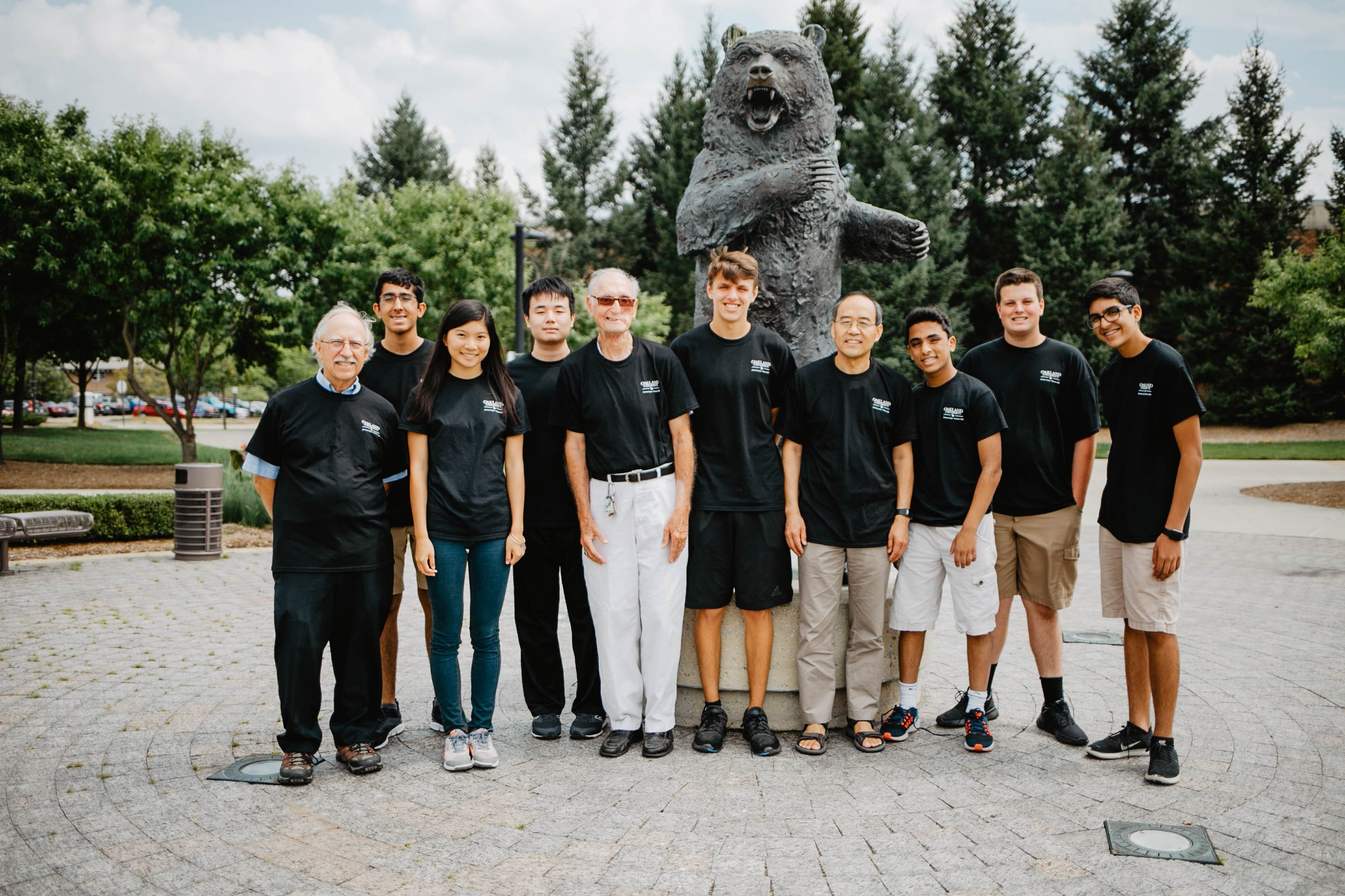 Group of Actuarial Science campers with leaders in front of Grizz statue.
