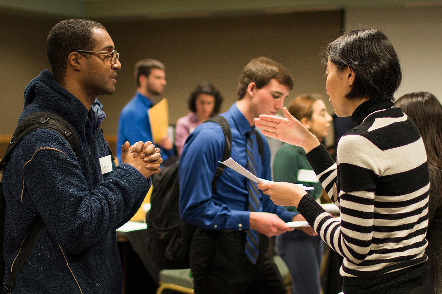 woman talking to a male student with other people in the background at the business major & minor expo
