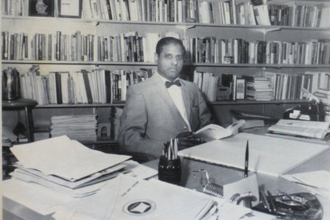 Sid Mittra reading a book at his desk