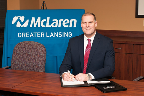 Casey Kandow seated with McLaren Greater Lansing backdrop