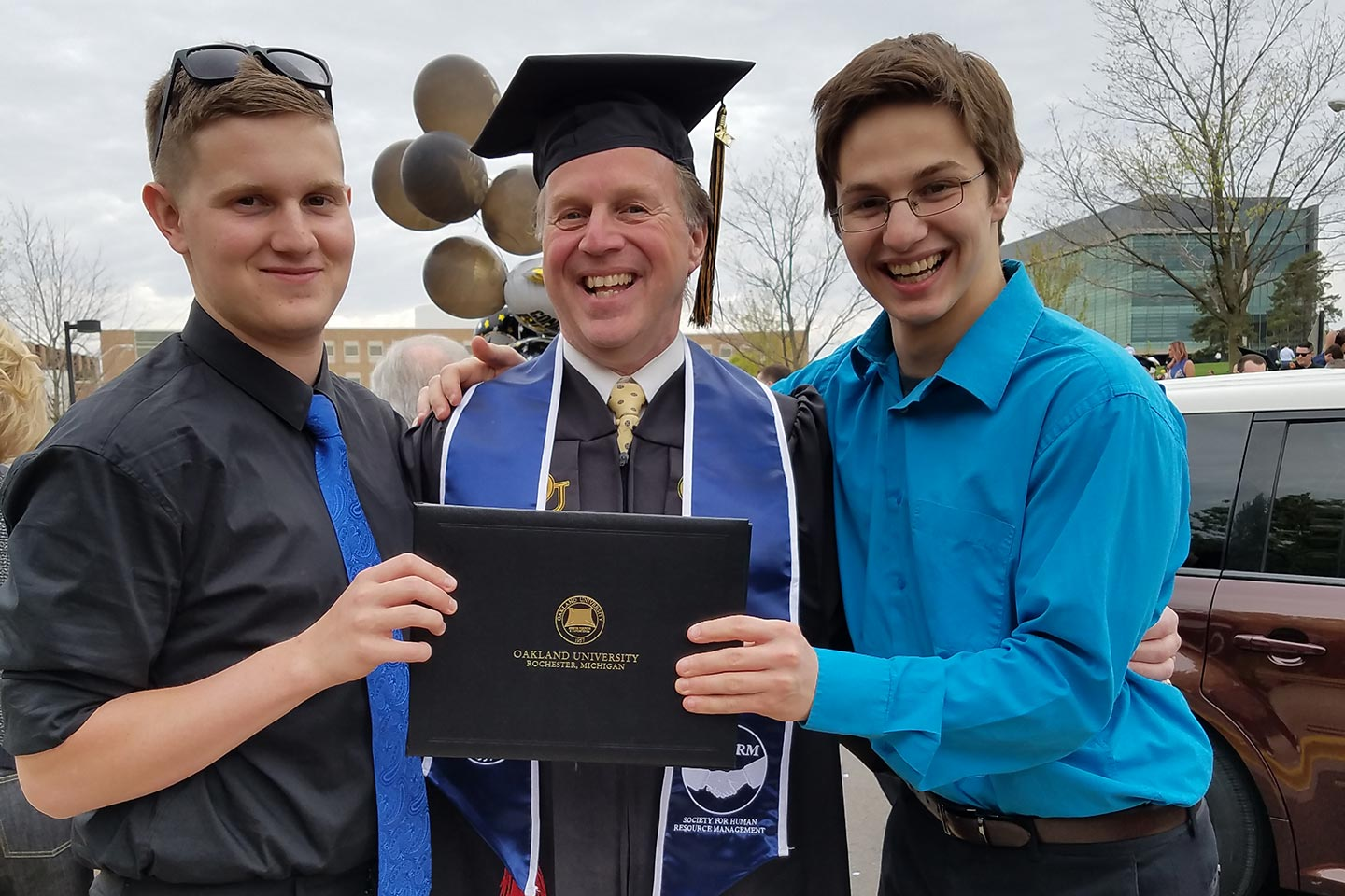 Richard Morrow, H R M '17, wearing a cap and gown and holding his diploma, with two of his sons at his Spring 2017 graduation