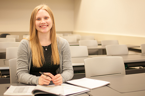 Avery Ragatzki seated at a desk in an empty classroom