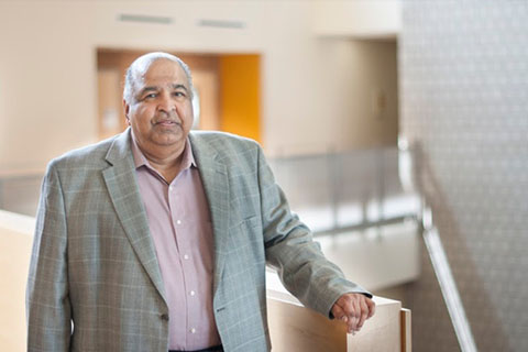 Ravi Parameswaran, Ph.D. leaning against a railing at the top of a stairway