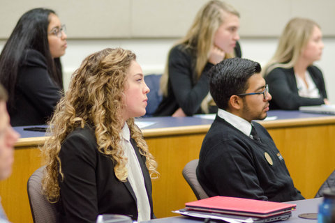 students in black professional attire, seated in rows in a classroom, all looking forward