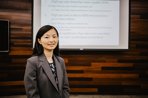 Sha Zhao standing in front of a projector screen, smiling at the camera