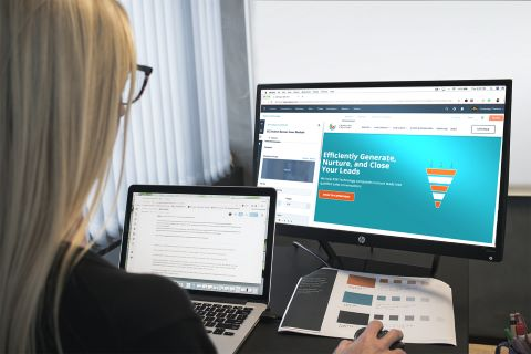 A person using a laptop and a second monitor to build a website.