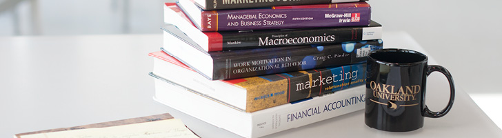 Business text books in a stack on a table with an Oakland University coffee mug
