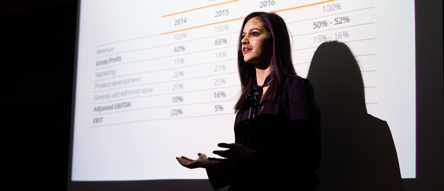 A young woman standing in front of a projector screen displaying percentage data.