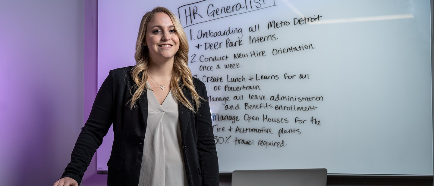 "A young woman standing in front of a white board with ""HR Generalist"" and a list of tasks written on it."