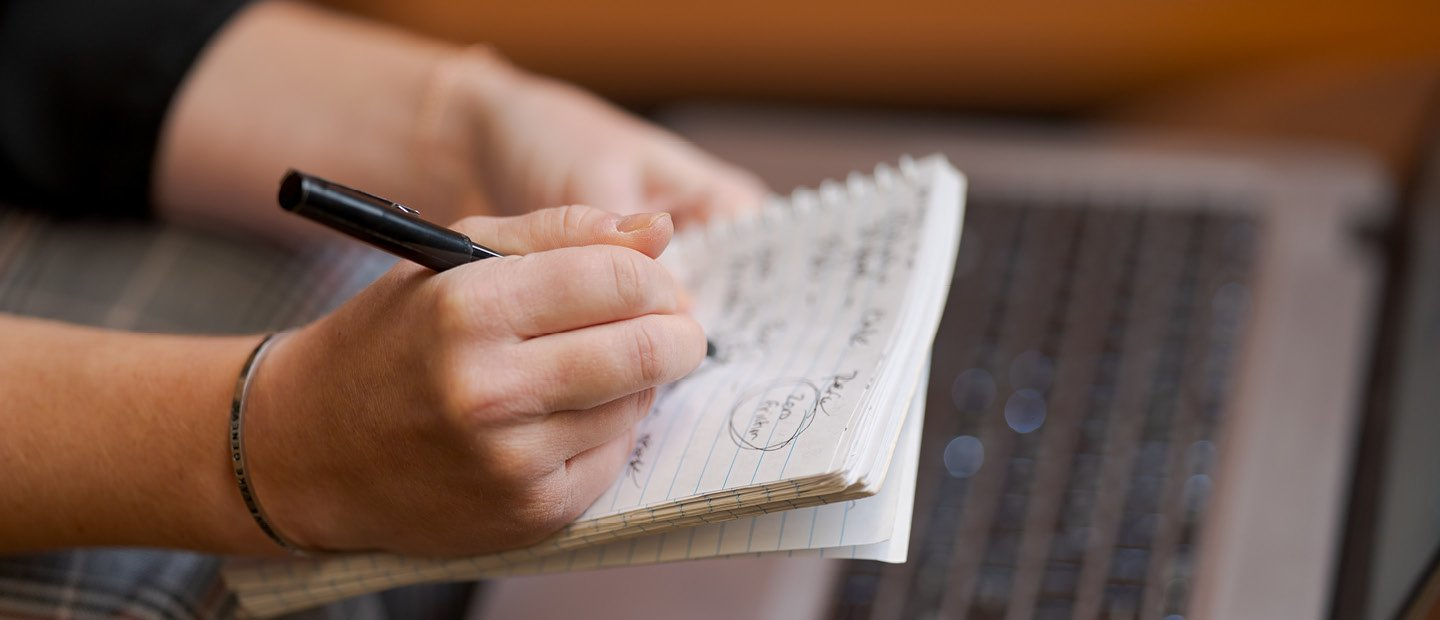 A person's hands writing on a notepad, held over an open laptop.