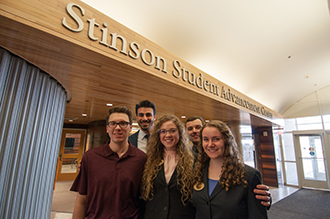 Small group of Business Scholars. Five undergraduate students. three in front, two in back. In front of Stinson Center in Elliott Hall.