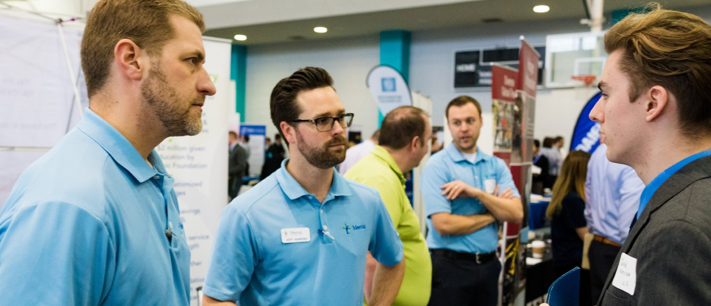 Men in blue shirts with name tags talking to a man in a suit at a career fair with display tables in the background