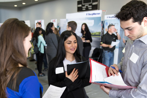 people in professional clothing, wearing name tags and holding folders at the career fair