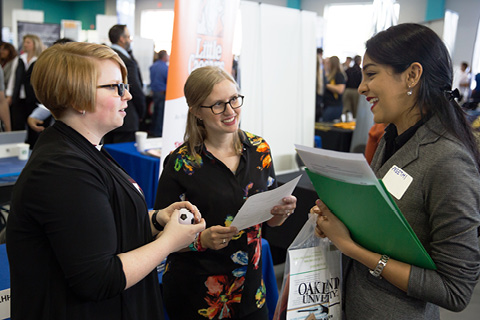 A photo of three people talking at a major and minor fair
