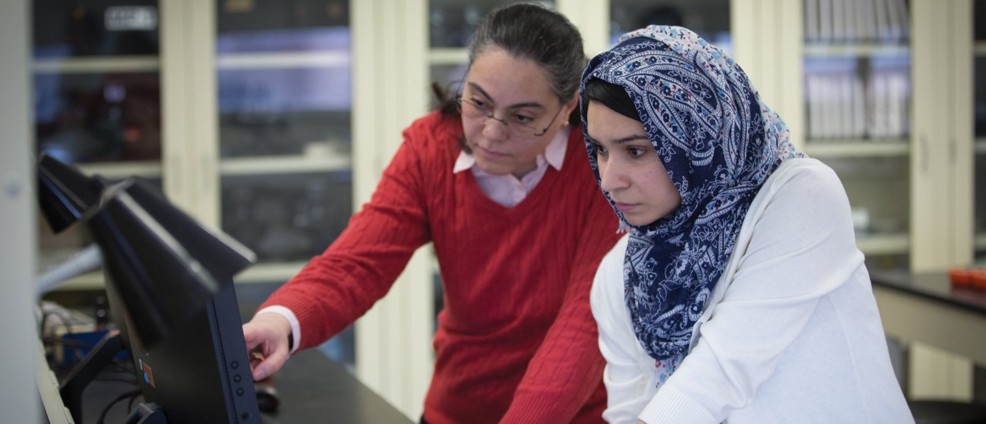 Two women standing at a desk, looking at a computer screen together.
