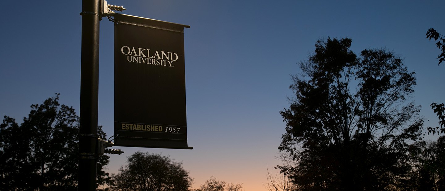 An Oakland University banner hanging on a pole outside at twilight.