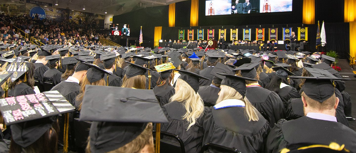 A photo of graduates in caps and gowns, facing a stage.