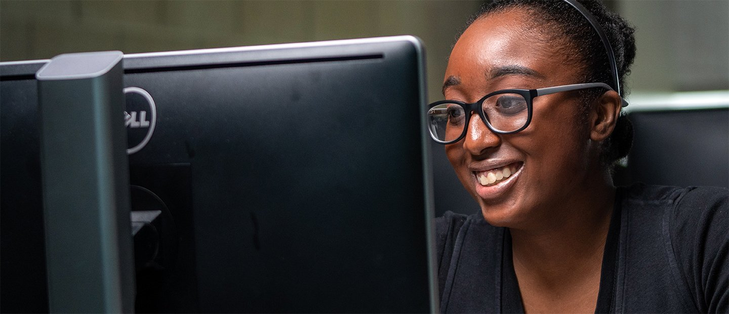 A young woman smiling, looking at a computer screen.