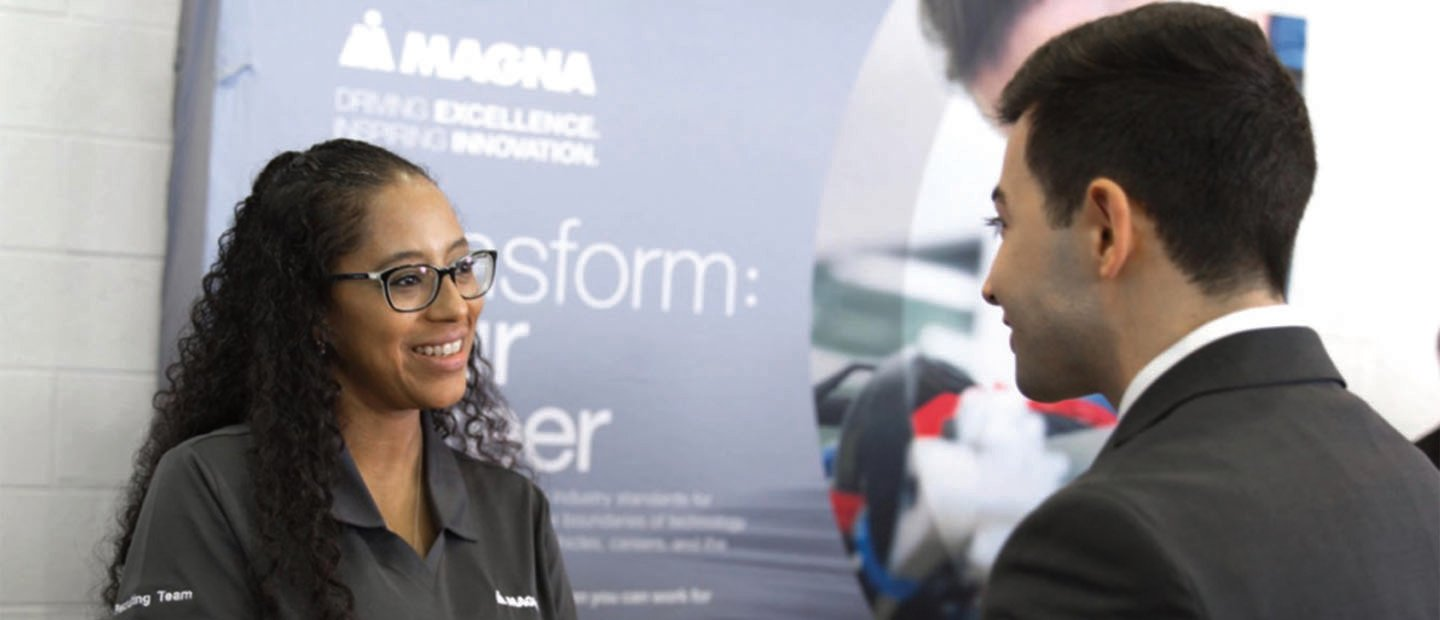 "man and woman facing each other, smiling, in front of a sign that says ""Magna"""
