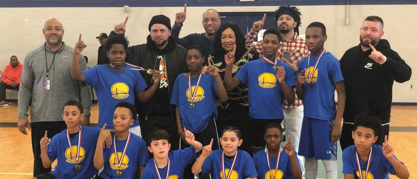 group photo of kids wearing medals and coaches, all holding up their index finger like the number one