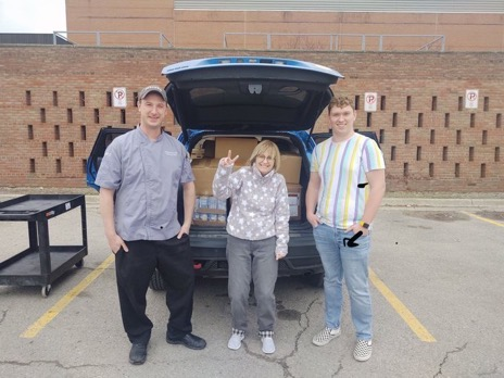 Three Grizz Pantry workers standing behind an SUV full of boxes of food with the tailgate open