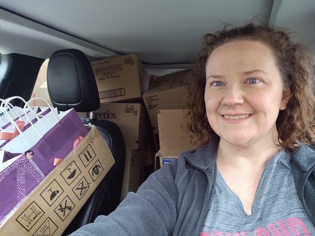 A woman driving a car that is full of boxes of food