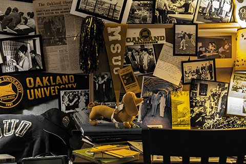 Oakland University banners, postcards, newspaper articles and memorabilia on a wall and desk