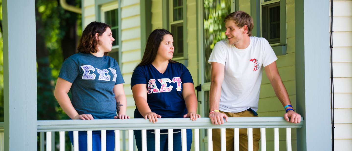 students on a porch wearing shirts with Greek letters