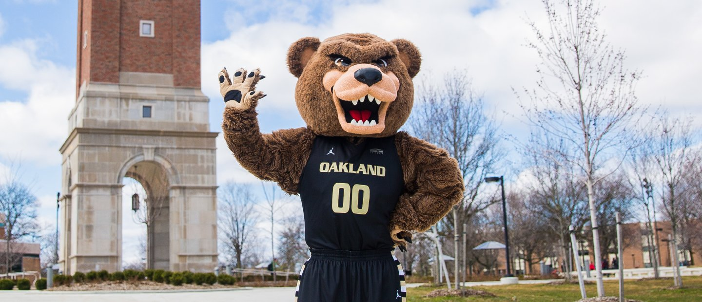 The Grizz bear mascot standing outdoors, waving, with Elliott Tower in the background