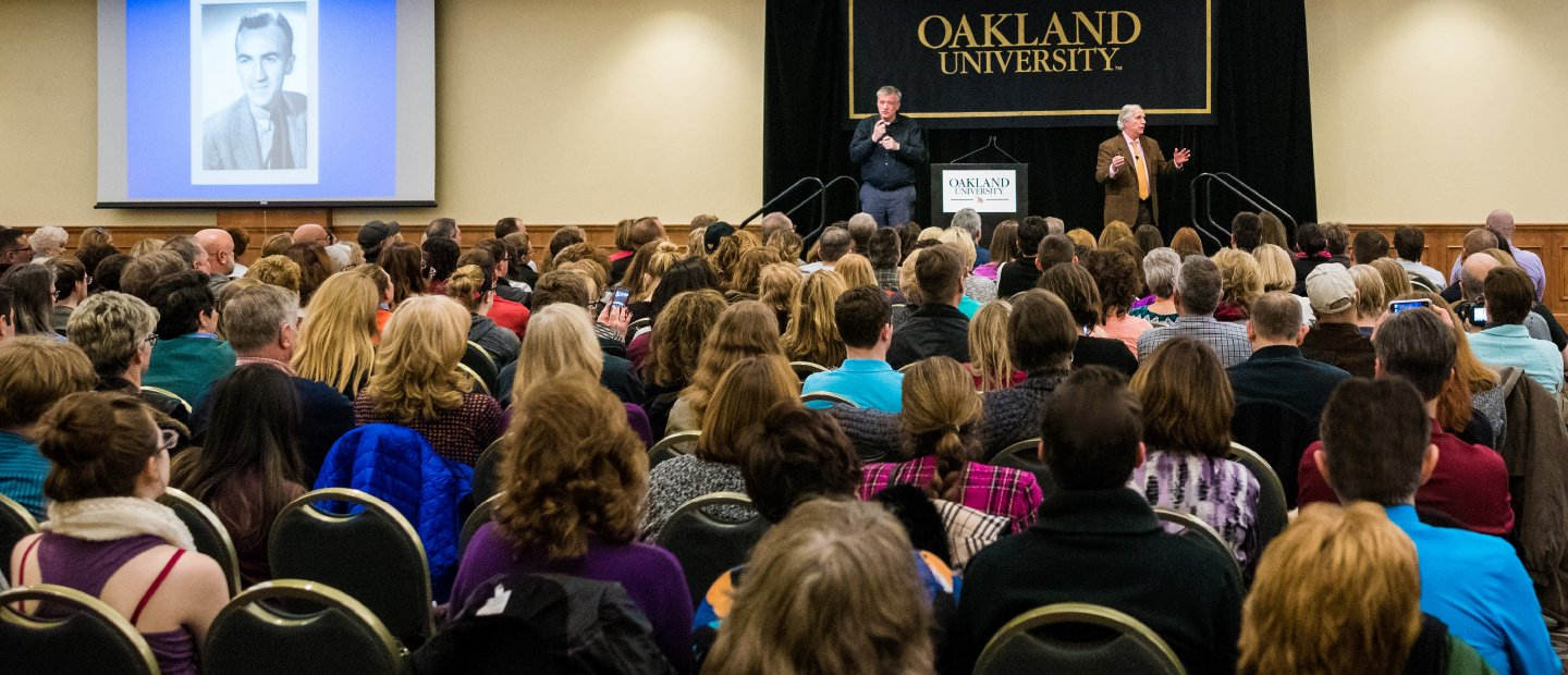 two men standing in front of a black Oakland University banner, addressing a seated audience