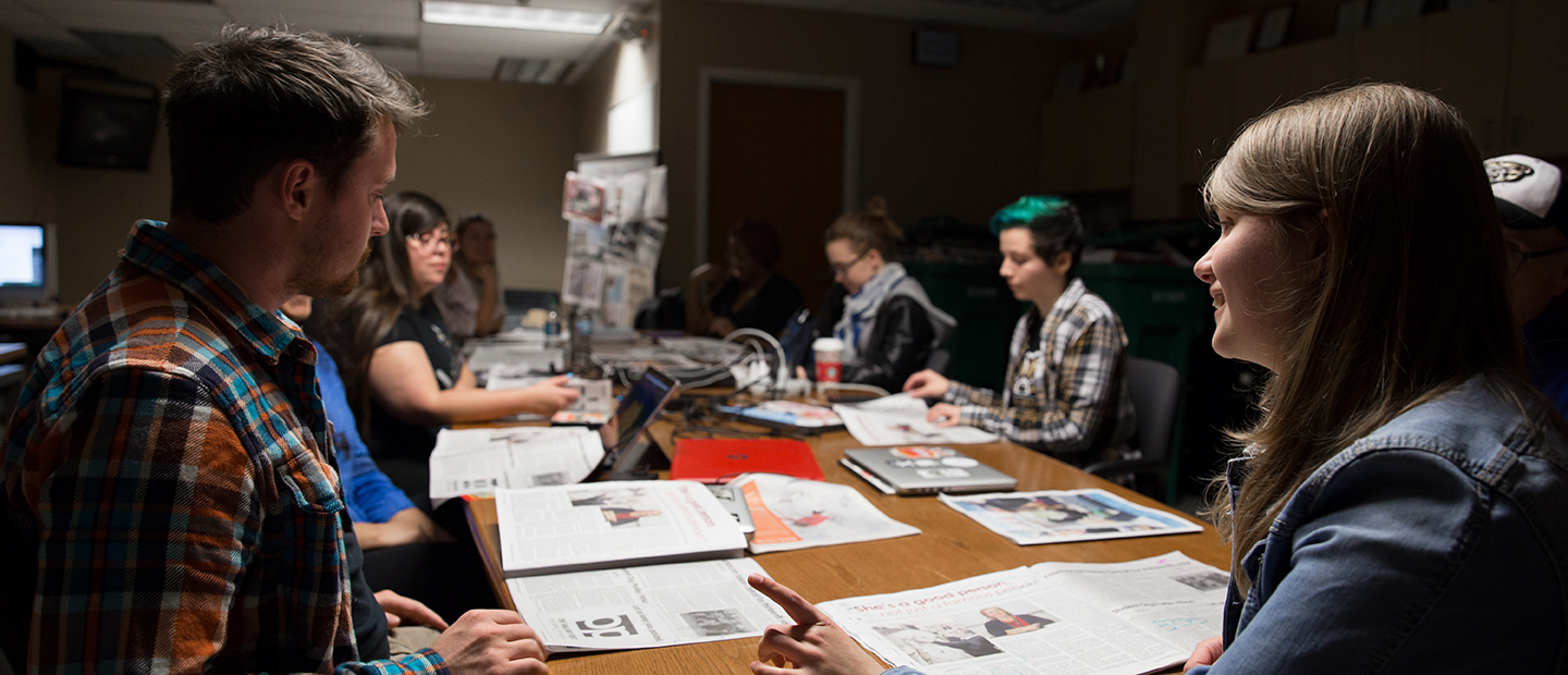group of students sitting around a table covered with open newspapers