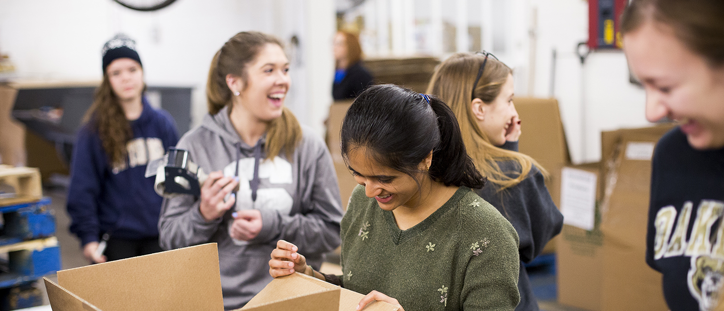image of five women in a warehouse who are laughing and packing boxes