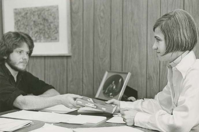 1970s photo of BillieDeMont handing a book to a student