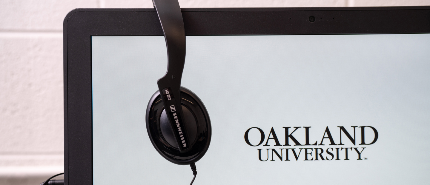 computer screen with Oakland University displayed and headphones hanging over the top