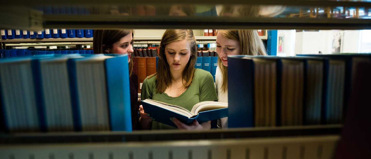 three young women looking at an open book among shelves of books in a library