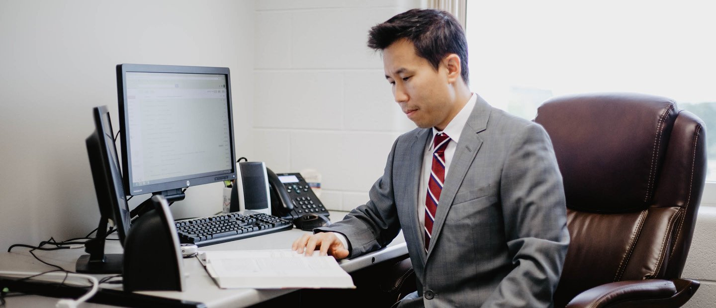 man in a suit at a desk with a computer and an open notebook