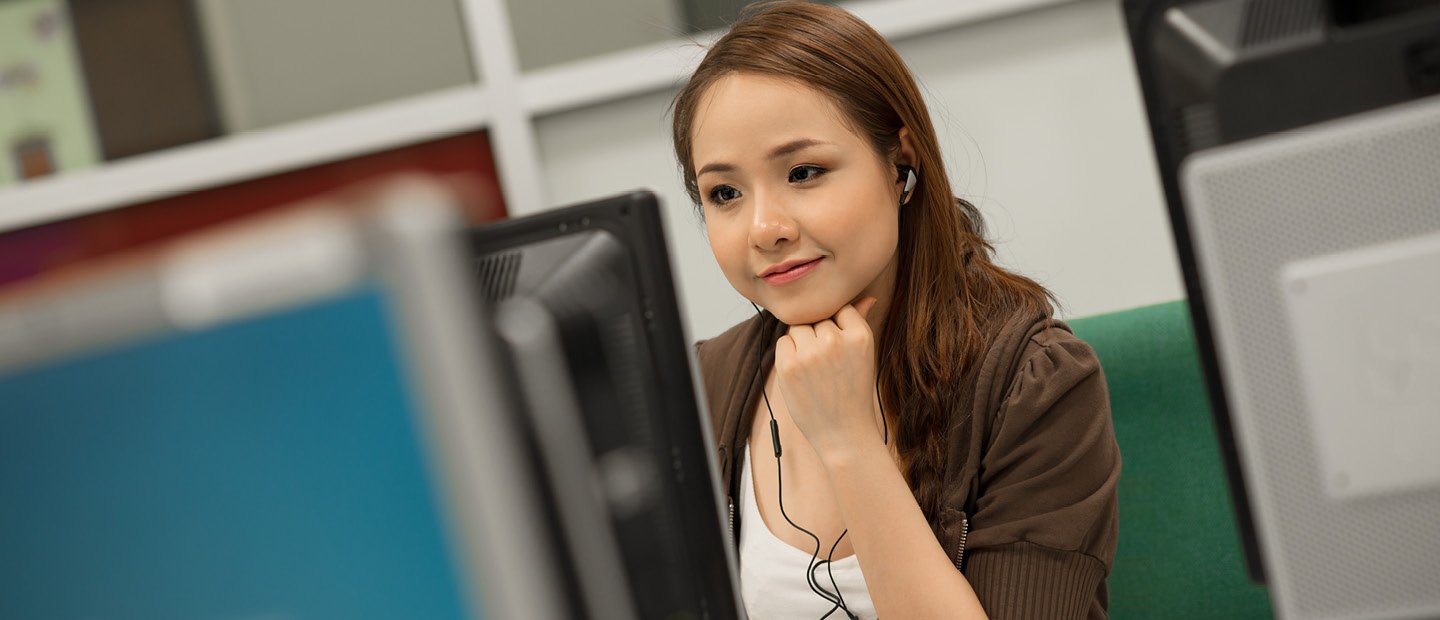 young woman wearing headphones, seated at a computer
