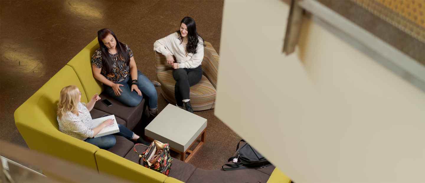 An aerial photo of three women seated on a couch, in conversation.