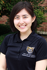 woman in a black Oakland University shirt, smiling at the camera